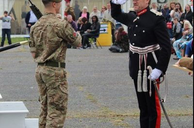The Lord-Lieutenant salutes Cadet Regimental Sergeant Major Teddy Hukins before presenting him with one of two awards at Bassingbourn Barracks on 9th June 2018
